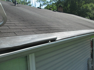ROOFER DAMAGE: GUTTER HELMET DENTED AND OUT OF ALIGNMENT